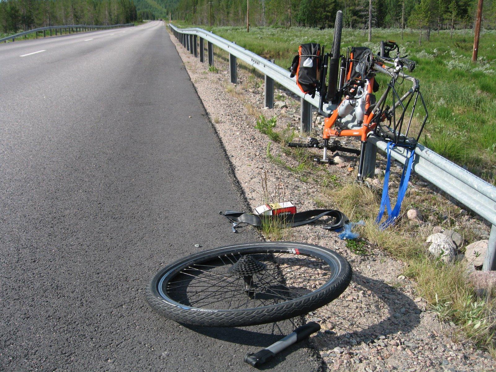 Reparando un pinchazo en la bicicleta en la ruta que cruza Suecia