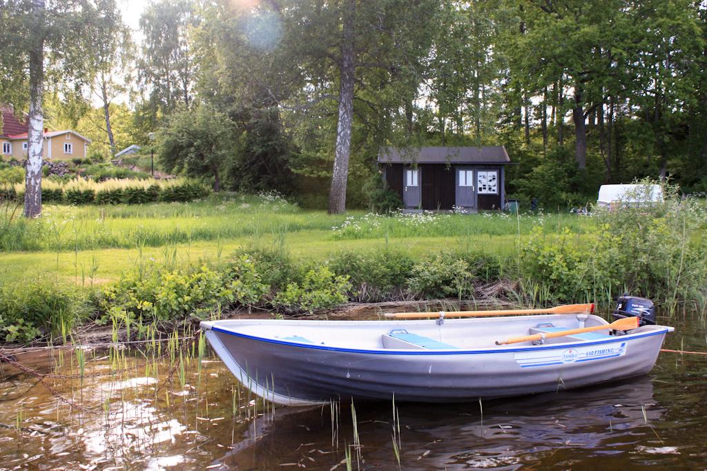 Barca amarrada junto a casitas en el lago Bunn, Småland, Suecia <br> Foto: Israel Úbeda